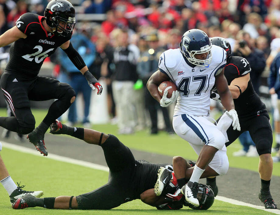 Connecticut fullback Reuben Frank (47) is tackled by Cincinnati defenders Nick Temple, bottom, JK Schaffer, right, and safety Drew Frey (26) in the first half of an NCAA college football game, Saturday, Dec. 3, 2011, in Cincinnati, Ohio. (AP Photo/Al Behrman) / AP