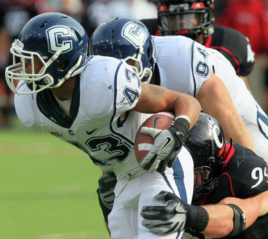 Connecticut running back Lyle McCombs (43) is tackled for a loss by Cincinnati defensive tackle Derek Wolfe (95) in the first half of an NCAA college football game, Saturday, Dec. 3, 2011, in Cincinnati, Ohio. (AP Photo/Al Behrman) / AP