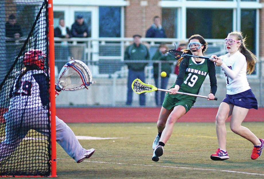 Hour photo/Erik TrautmannNorwalk's Brianna Fitzgerald, center, takes a shot on goal while defended by Brien McMahon's Amanda Donofrio, right, and goalie Michele Petrucci during Saturday night's clash of the crosstown rivals. Norwalk scored a 15-5 victory. / (C)2013, The Hour Newspapers, all rights reserved