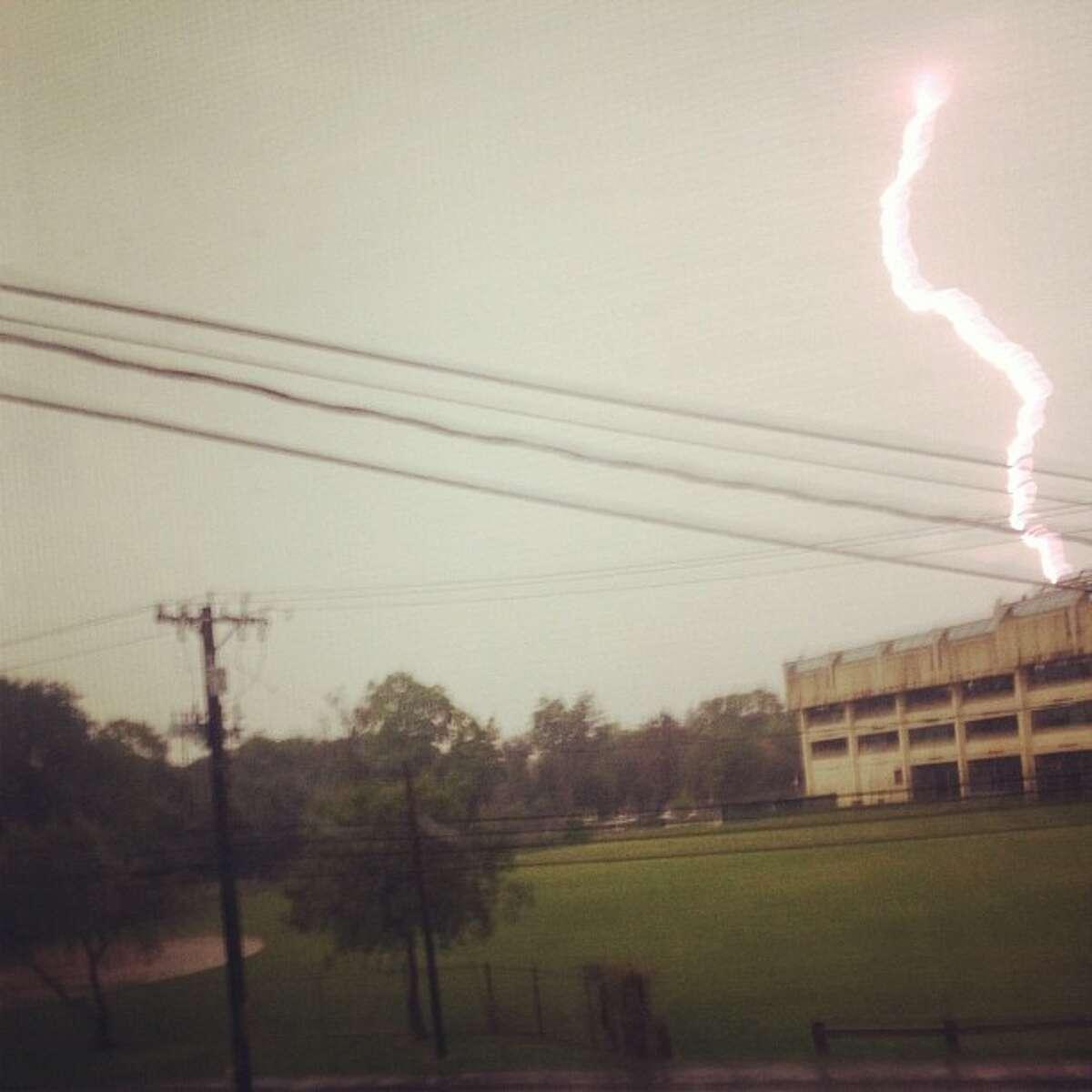 Lightning strikes over Norwalk High School Monday morning.