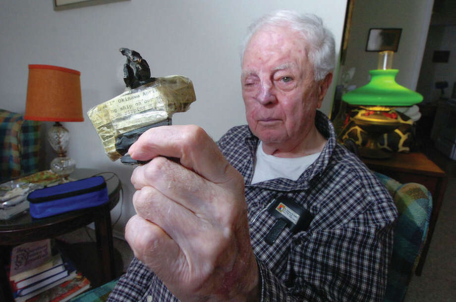 Hour Photo/ Alex von Kleydorff. World War II Veteran Tom Collins holds the fragment removed from him after shhoting down a Japanese plane that was attacking his ship in Okinawa. / 2011 The Hour Newspapers