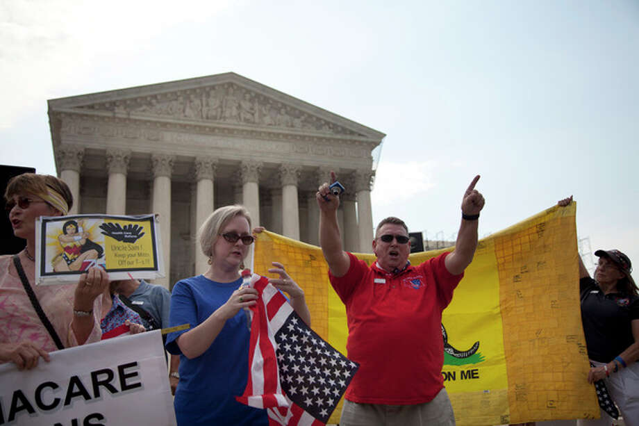 Demonstrators stand outside the Supreme Court in Washington, Monday, June 25, 2012. The Supreme Court is meeting Monday to issue opinions in some of the handful of cases that remain unresolved. (AP Photo/Evan Vucci) / AP