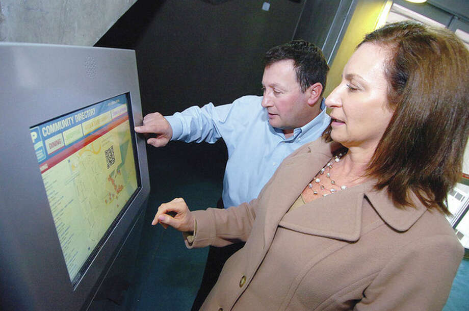 Hour photos / Alex von KleydorffNorwalk Parking Authority Director Kathryn Hebert and General Manager David Lew explore the new informational kiosk. Right, the community directory. / 2013 The Hour Newspapers