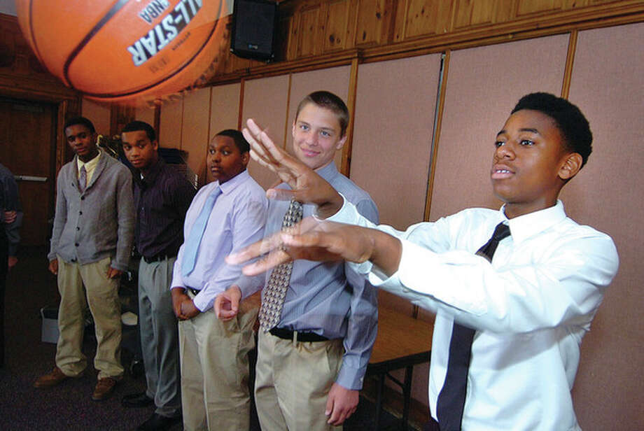 Hour Photo/ Alex von KleydorffPotential youth employee Isaiah Snider throws a basketball back during introductions and questions part of the 'Give and Take Fast Break' Youth Job training with Malik Williams in the City Hall Community Room on Monday. / 2012 The Hour Newspapers