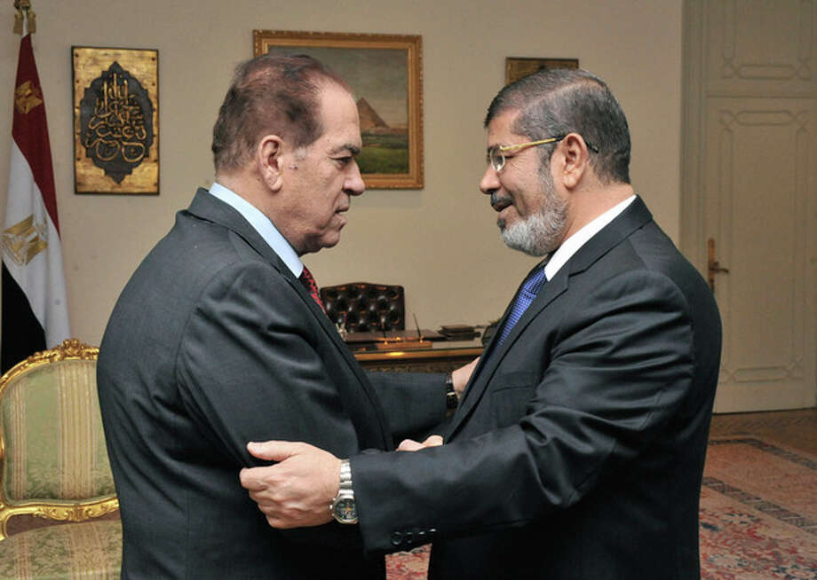 AP Photo/Middle East News Agency, HOThe Egyptian official news agency, caretaker Prime Minister Kamal el-Ganzouri, left, shakes hands with newly elected President Mohammed Morsi in Cairo, Egypt, Monday, June 25. / Middle East News Agency