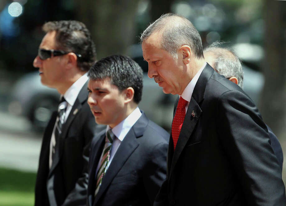 """Turkish Prime Minister Recep Tayyip Erdogan, right, arrives for a cabinet meeting in his office in Ankara, Turkey, Monday, June 25, 2012. Upon Turkey's request, NATO will hold a meeting Tuesday in Brussels over article 4 of its charter concerning Friday's incident, when a Turkish warplane was shot down by Syria. Syria's Foreign Ministry spokesman Jihad Makdissi said Monday his country has """"no hostility"""" toward Turkey as tensions soar between the former allies three days after Syria shot down a Turkish plane. (AP Photo) / AP"""