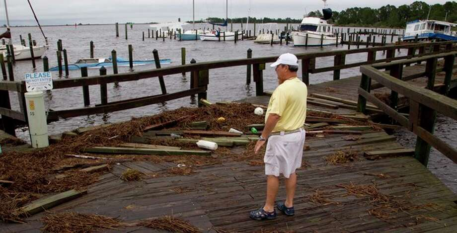 Mark Mitchell surveys the damage to boats at the Rock Landing Marina in Panacea, Fla., Tuesday, June 26, 2012. High winds and heavy rains spawned by the approaching Tropical Storm Debby caused the damage. (AP Photo/Dave Martin) / AP