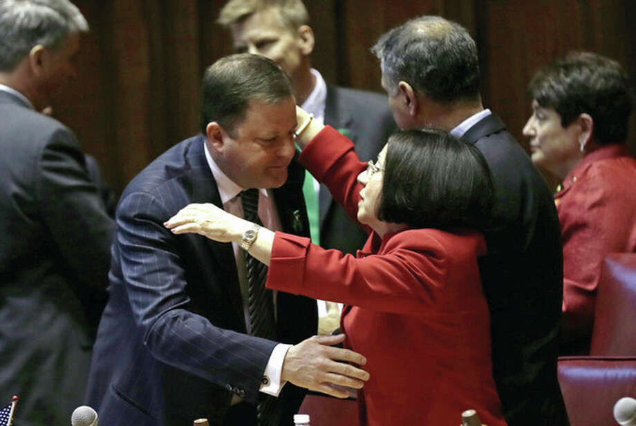 AP photo / Charles KrupaSenate Minority Leader John McKinney, R-Fairfield, who represents Newtown, left, is embraced by Sen. Toni Boucher, who represents several Fairfield County towns, after the passage of a gun-control bill in the Senate chamber at the Capitol in Hartford Wednesday. / AP