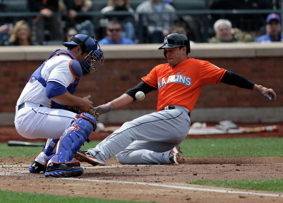 New York Mets' Anthony Recker, left, tries to catch the ball while Miami Marlins' Greg Dobbs slides safely home during the third inning of the baseball game at CitiField Sunday, April 7, 2013, in New York. (AP Photo/Seth Wenig) / AP
