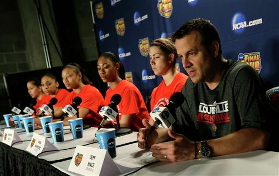 Louisville head coach Jeff Walz, right, and his players talk during a news conference for the women's NCAA Final Four college basketball tournament final, Monday, April 8, 2013, in New Orleans. Louisville plays Connecticut in the championship game on Tuesday. (AP Photo/Dave Martin) / AP