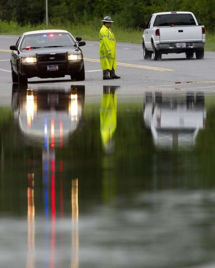 A Florida Highway Patrolman warns motorists about high water in Medart, Fla., Tuesday, June 26, 2012. Heavy rains from the approaching Tropical Storm Debby caused wind and rain damage. (AP Photo/Dave Martin)