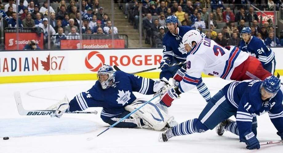 Toronto Maple Leafs goalie James Reimer, left, makes a diving save on a shot by New York Rangers forward Ryane Clowe, second from right, as Maple Leafs forward Jay McClement, right, trips up Clowe during the third period of their NHL hockey game in Toronto, Monday, April 8, 2013. (AP Photo/The Canadian Press, Nathan Denette) / The Canadian Press