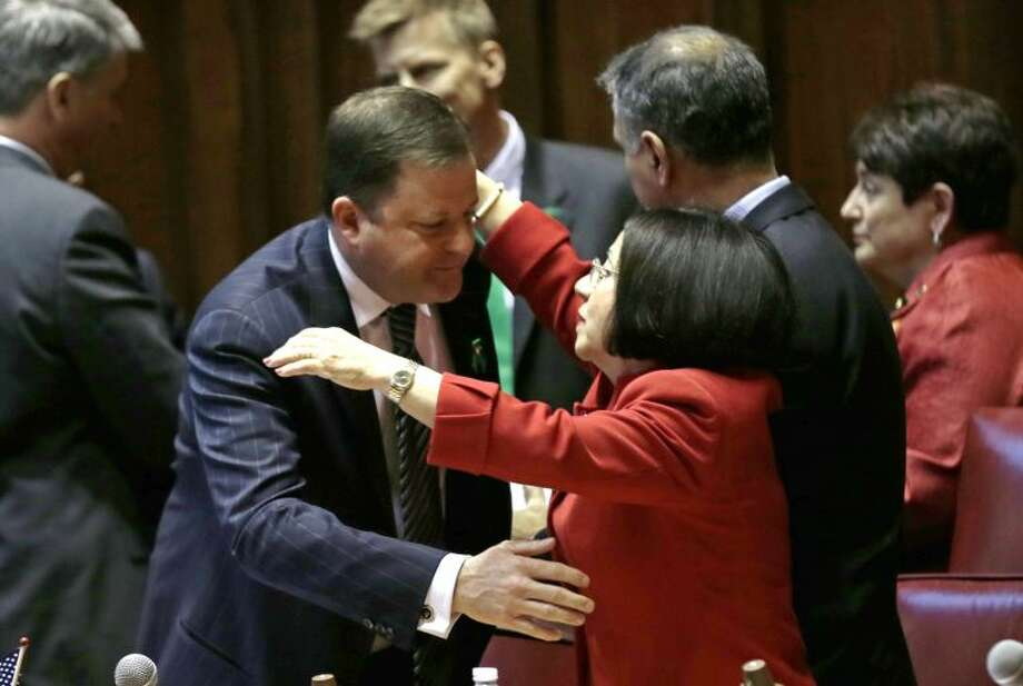 Senate Minority Leader John McKinney, R-Fairfield, who represents Newtown, Conn., left, is embraced by Conn. Sen. Toni Boucher, who represents western coast towns of Conn., after the passage of a gun-control bill in the Senate chamber at the Capitol in Hartford, Conn., Wednesday, April 3, 2013. The bill passed the Senate and goes onto the Conn. Houses for approval. Hundreds of gun rights advocates are gathering at the statehouse in Hartford ahead of a vote in the General Assembly on proposed gun-control legislation. (AP Photo/Charles Krupa)
