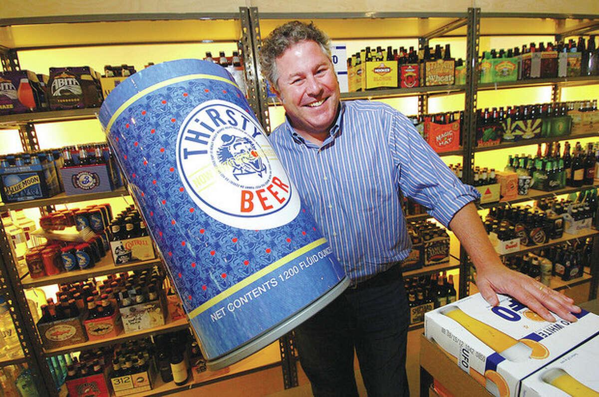 Hour Photo/ Alex von Kleydorff. Bottlerocket Wine and Spirit owner Tom Geniesse and 1200 fluid ounces of Thirsty Beer in his new Westport location.