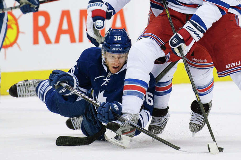 Toronto Maple Leafs defenseman Carl Gunnarsson, left, battles for the puck against New York Rangers forward Rick Nash, right, during the first period of their NHL hockey game in Toronto, Monday, April 8, 2013. (AP Photo/The Canadian Press, Nathan Denette) / The Canadian Press