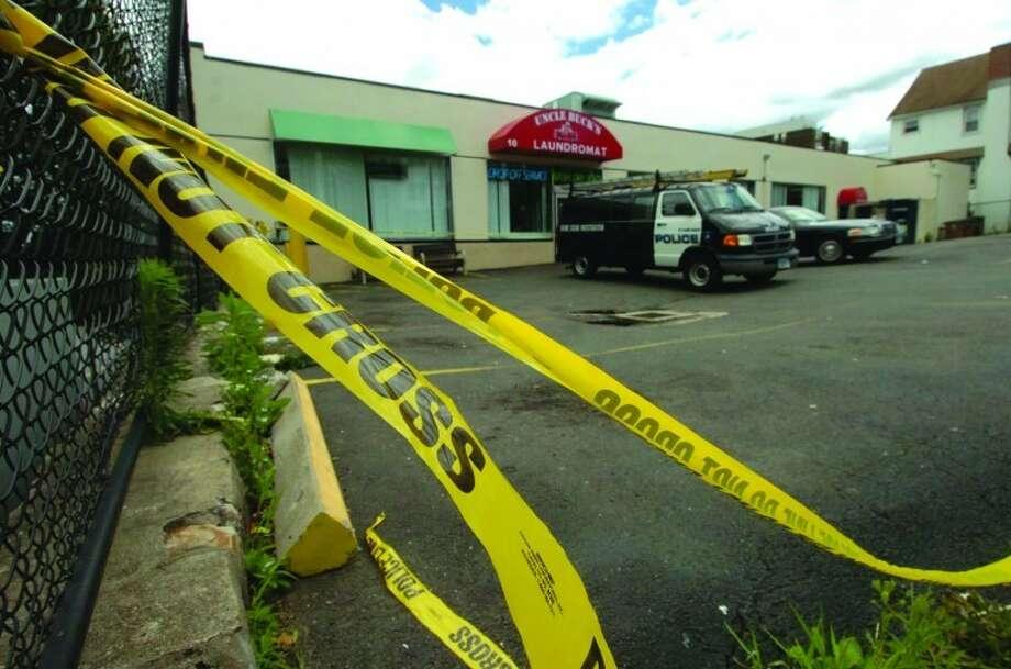 Hour Photo/ Alex von Kleydorff. Police investigate a homicide scene at Uncle Bucks Laundromat in Stamford on June 25, 2011.