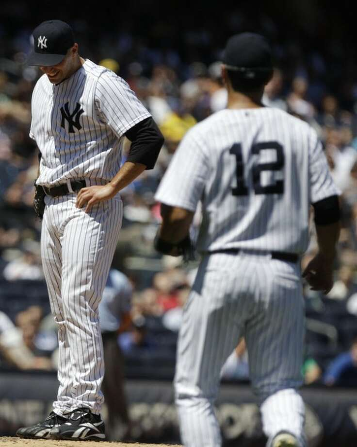 New York Yankees' Eric Chavez (12) approaches the pitchers mound as starting pitcher Andy Pettitte grimaces during the fifth inning of a baseball game against the Cleveland Indians Wednesday, June 27, 2012, in New York. (AP Photo/Frank Franklin II)