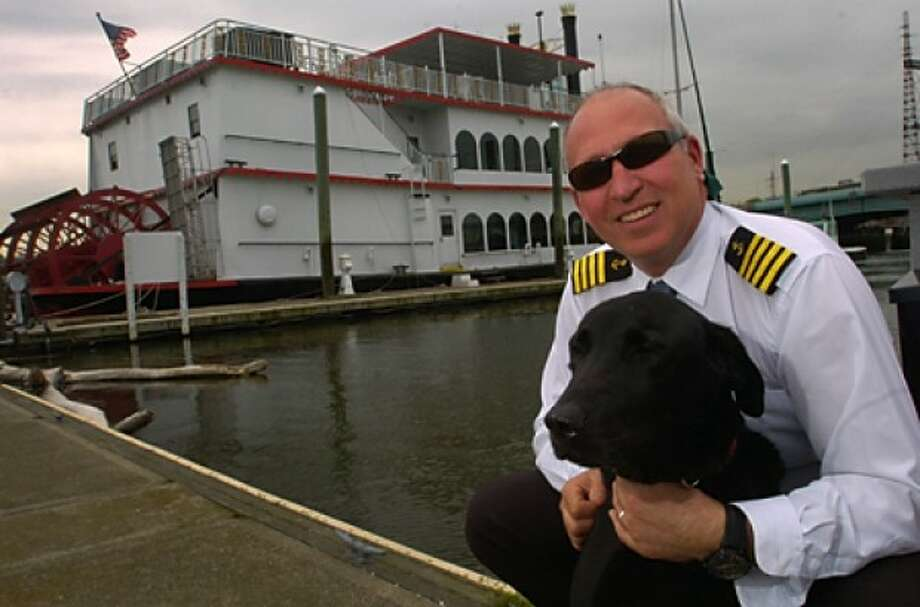 Captain Ken Hart, his dog, Pierce, with his boat the Island Belle, which will start ferrying between Northport Long Island and South Norwalk this summer along with charter avalability for special events. Hour photo / Erik Trautmann
