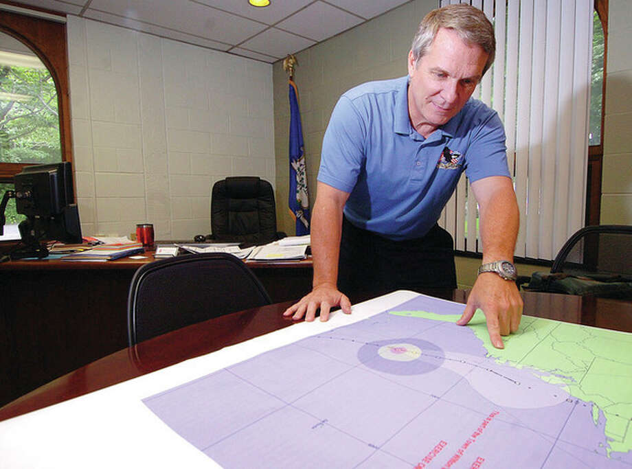 Photo by Alex von KleydorffWilton Fire Chief Paul Milostz looks over a map showing the track of Hurricane Sophie, a mock hurricane of Wilton's emergency service administrators used as part of the town's hurricane drill last week. / 2012 The Hour Newspapers