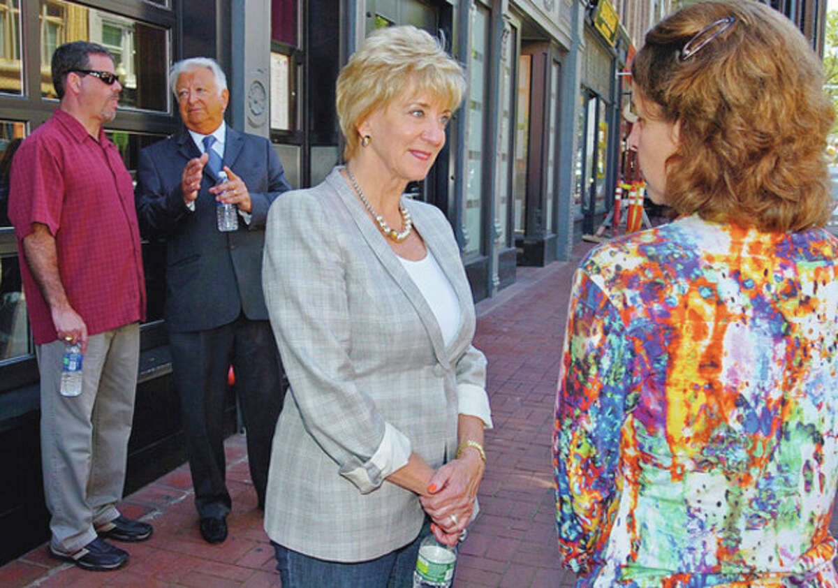 Hour photos / Erik Trautmann GOP congressional candidate Linda McMahon tours South Norwalk Wednesday with Mayor Richard Moccia, second from left, and chats with Stephanie Pelletier, right, marketing director of TD SoNo Partners. Man at far left is unidentified.