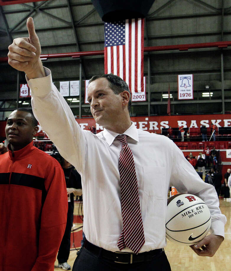 FILE - In this Jan. 28, 2012, file photo, Rutgers coach Mike Rice waves as he holds a ball presented to him for his 100th career win after Rutgers defeated Cincinnati in an NCAA college basketball game in Piscataway, N.J. ESPN's airing on Tuesday, April 2, 2013, of a videotape of Rutgers basketball coach Mike Rice using gay slurs, shoving and grabbing his players and throwing balls at them in practice over the past three seasons has the university's athletic director reconsidering his decision not to fire the coach. Scarlet Knights AD Tim Pernetti was given a copy of the video in late November by a disgruntled former employee, and he suspended Rice for three games, fined him $50,000 and made him undergo anger management classes for inappropriate behavior after investigating it. (AP Photo/Mel Evans,file) / AP