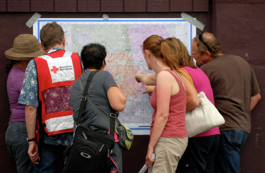 Evacuees of the Waldo Canyon Fire look at the most recent map of the fire's progression at the Cheyenne Mountain High School evacuation center on Wednesday, June 27, 2012, in Colorado Springs, Colo. The wildfire doubled in size overnight to about 24 square miles (62 square kilometers), and has so far forced mandatory evacuations for more than 32,000 residents. (AP Photo/Bryan Oller) / fr81708 AP