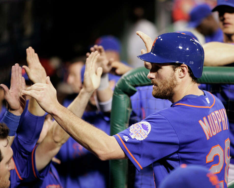 New York Mets' Daniel Murphy returns to high-fives in the dugout after scoring on an single to center by Lucas Duda in the third inning of a baseball game with the Philadelphia Phillies, Monday, April 8, 2013, in Philadelphia. (AP Photo/Tom Mihalek) / FR148949 AP