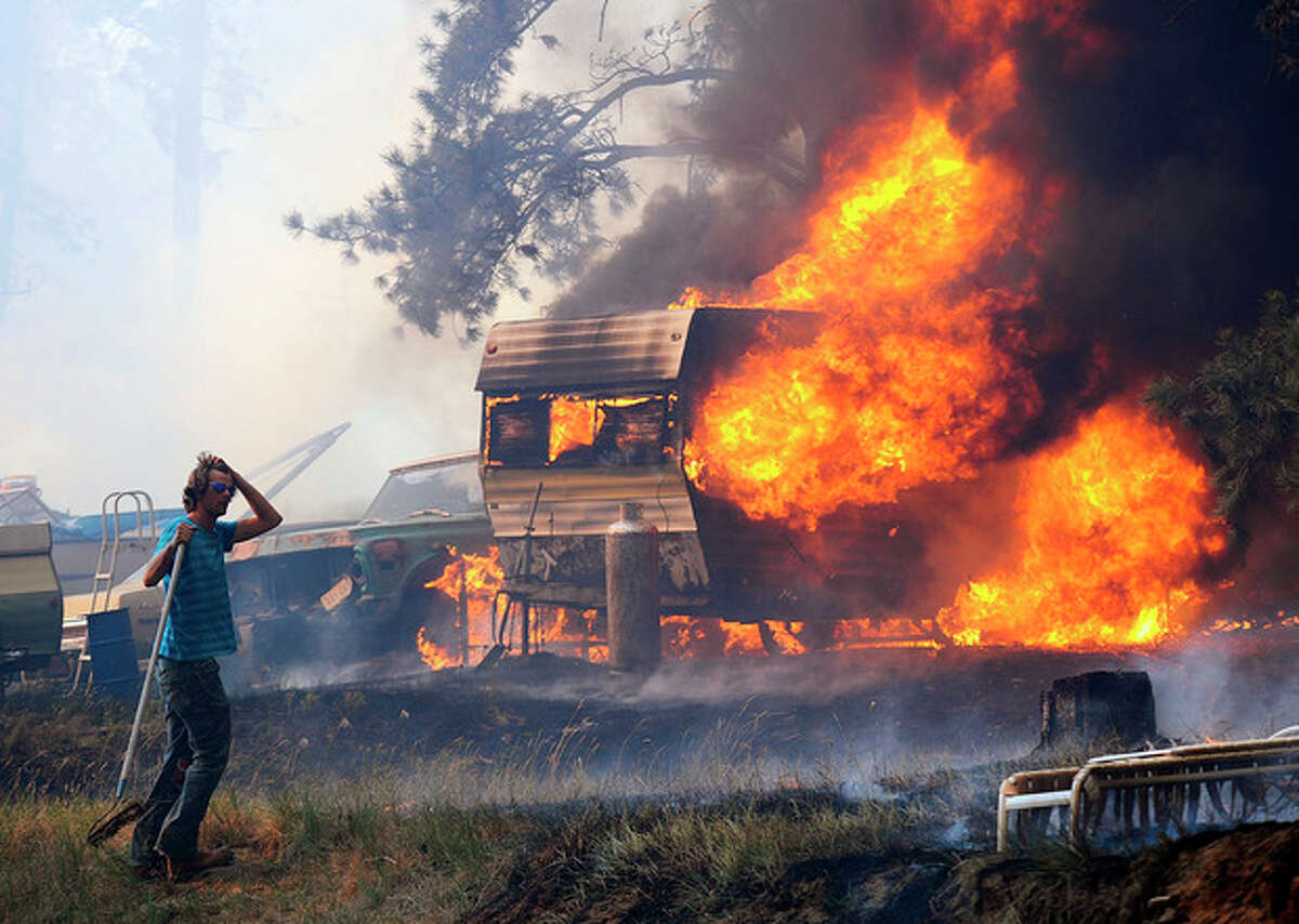 Volunteers and firefighters from the Dean Creek Fire Department work to save a home south of Roundup, Mont. on June 26, 2012. Hundreds of families were forced from their homes south of Roundup as a fire pushed by strong winds burned more than 18,000 acres. (AP Photo/The Billings Gazette, Larry Mayer)