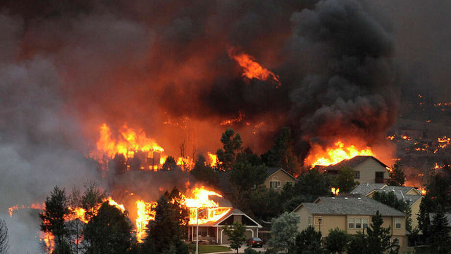 An entire neighborhood burns near the foothills of Colorado Springs, Colo. on Tuesday, June 26, 2012. A towering wildfire destroyed dozens of houses overnight, though the intensity of the blaze kept officials Wednesday from being able to fully assess the damage to the state's second-largest city. (AP Photo/The Denver Post, Helen H. Richardson) MAGS OUT; TV OUT; INTERNET OUT / (C) 2011 The Denver Post, MediaNews Group