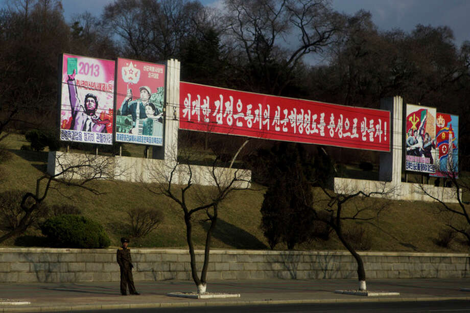 """A North Korean soldier stands beneath roadside propaganda which reads """"Let's Uphold the Military First Revolutionary Leadership of the Great Comrade Kim Jong Un With Loyalty"""" in Pyongyang on Tuesday, April 9, 2013. (AP Photo/David Guttenfelder) / AP"""