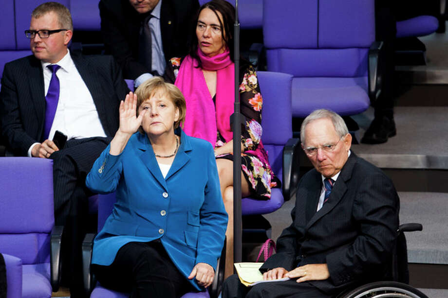 German Chancellor Angela Merkel, left, and Finance Minister Wolfgang Schaeuble right, seen during the debate after Merkel's speech for the upcoming EU summit at the German parliament Bundestag in Berlin, Wednesday, June 27, 2012. Germany faces increasing pressure to relent on its resistance to jointly issued eurobonds and other forms of debt-pooling ahead of a European Union summit Thursday. (AP Photo/Markus Schreiber) / AP