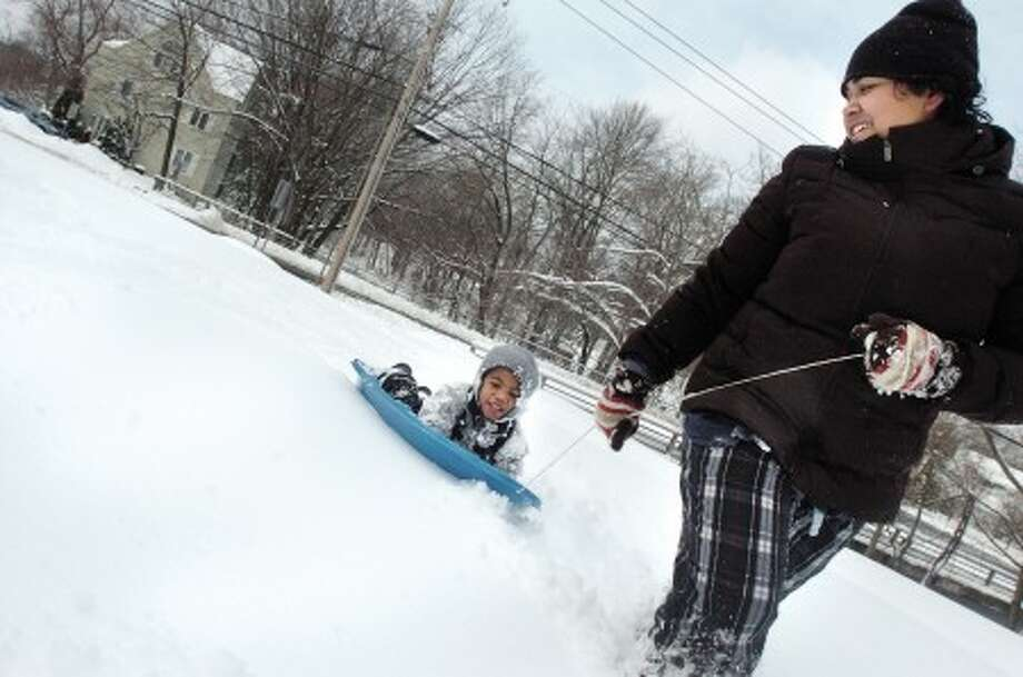 Dinushka Hubard tows her son Jonathan 4, down Bridge street towards home Wednesday in Stamford. photo/matthew vinci