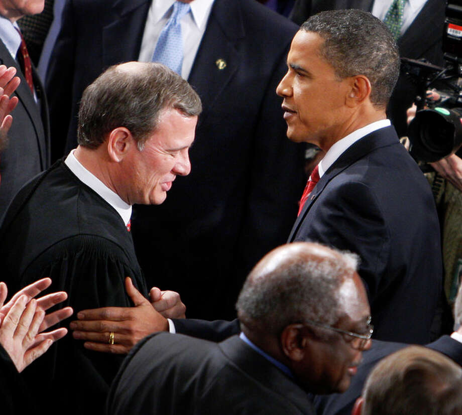 """FILE - In this Jan. 27, 2010 file photo, President Barack Obama greets Chief Justice John Roberts before he delivered his State of the Union Address on Capitol Hill in Washington. Breaking with the court's other conservative justices, Roberts announced the judgment that allows the law to go forward with its aim of covering more than 30 million uninsured Americans. Roberts explained at length the court's view of the mandate as a valid exercise of Congress' authority to """"lay and collect taxes."""" The administration estimates that roughly 4 million people will pay the penalty rather than buy insurance. (AP Photo/Charles Dharapak, File) / AP"""