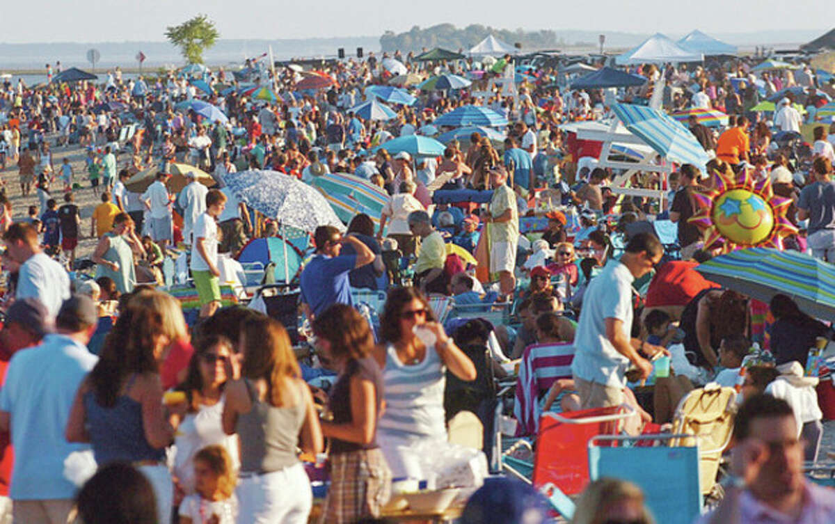 Hour file photo / Erik Trautmann Thousands crowd Compo Beach in Westport last July to see the fireworks display.