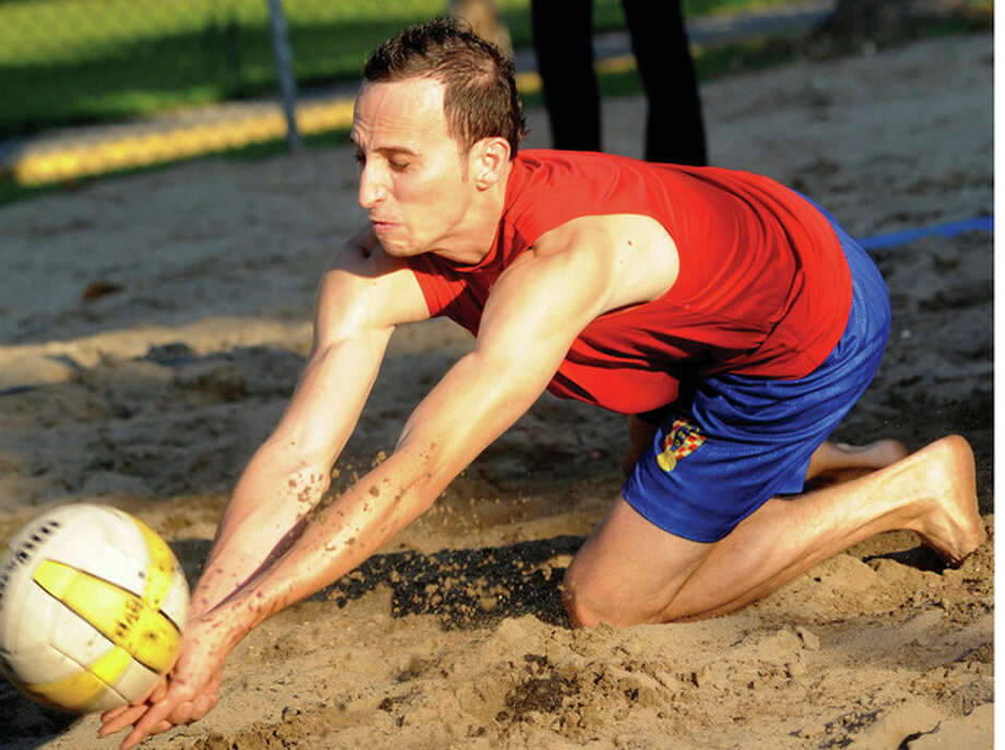 @White=[C] Hour photo/Matthew Vinci Julian Zuleta of Booth Financial gets down and dirty as he tries to make a save during Wednesday's Norwalk Rec beach volleyball action against the Fact Setters on court 1 at Calf Pasture Beach. / (C)2011, The Hour Newspapers, all rights reserved
