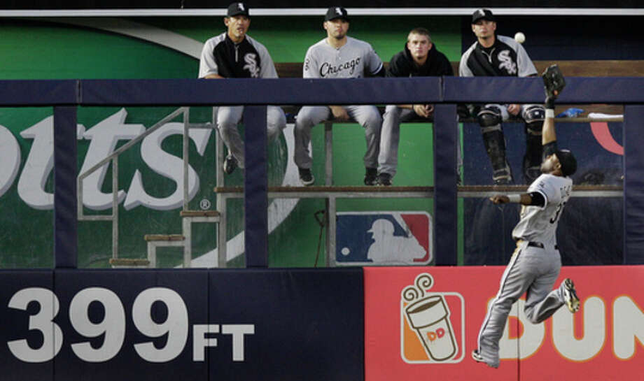 Members of the Chicago White Sox bullpen watch center fielder Alejandro De Aza leaping for New York Yankees' Alex Rodriguez's fifth-inning RBI-double during a baseball game at Yankee Stadium in New York, Thursday, June 28, 2012. (AP Photo/Kathy Willens) / AP