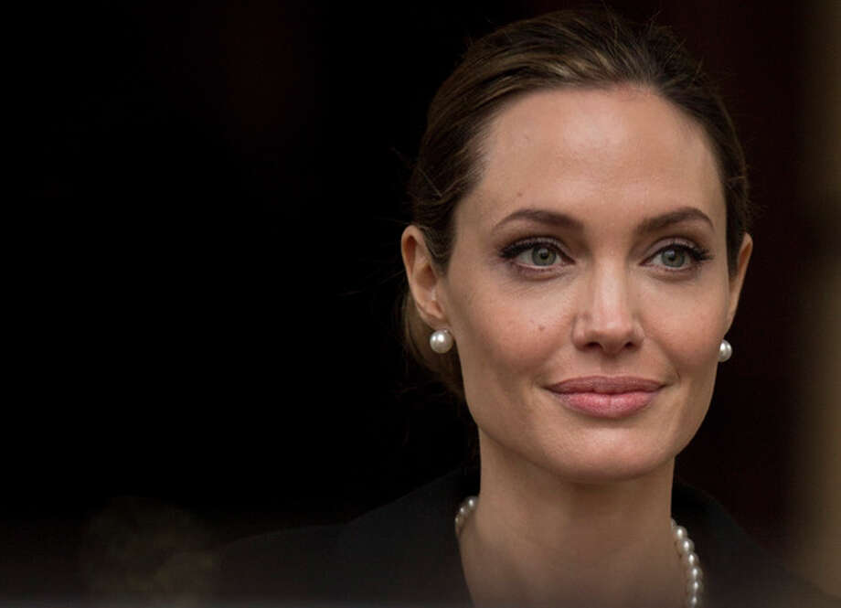 Angelina Jolie looks to the media as she leaves a G8 Foreign Ministers meeting on sexual violence against women in London, Thursday, April, 11, 2013. The ministers are meeting in London as Britain currently holds the G8 Presidency, with the heads of government G8 meeting set for June in Northern Ireland.(AP Photo/Alastair Grant) / AP
