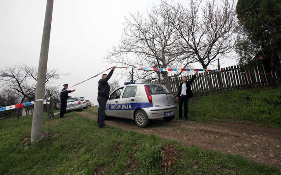 Police officers guard a house in village of Velika Ivanca, Serbia, Tuesday, April 9, 2013. A 60-year-old man gunned down 13 people, including a baby, in a house-to-house rampage in a quiet village on Tuesday before trying to kill himself and his wife, police and hospital officials said. (AP Photo/Darko Vojinovic) / AP