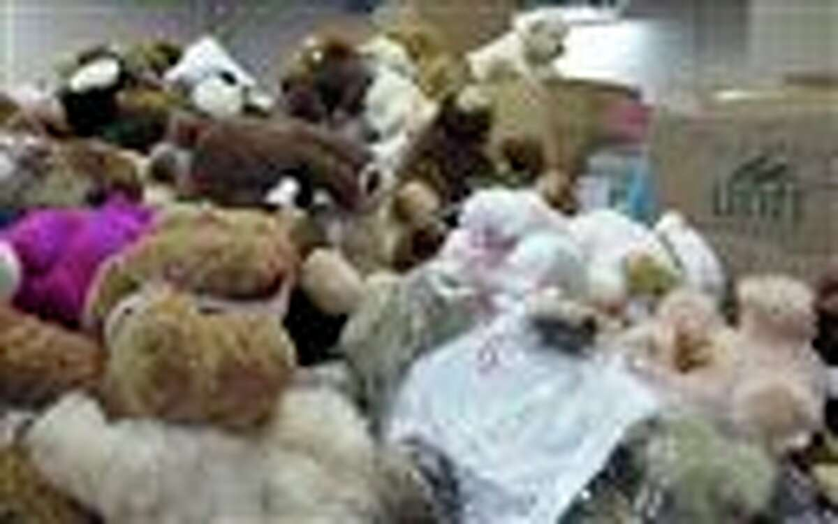 FILE - In this Monday, Dec. 31, 2012 file photo, piles of stuffed animals donated after 26 people were shot to death at Sandy Hook Elementary School, await sorting in a warehouse in Newtown, Conn. Newtown officials and families of those killed have given away 63,790 stuffed animals and thousands of other gifts that poured into the town in the weeks following the massacre. The final boxes of toys and school supplies were shipped out of the warehouse on March 29, 2013. (AP Photo/Pat Eaton-Robb)
