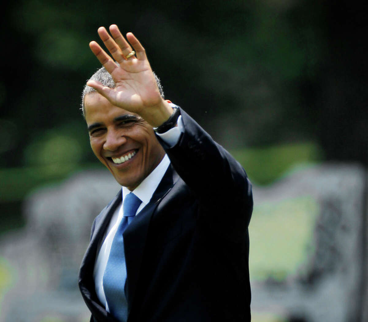 President Barack Obama waves as he walks across the South Lawn of the White House in Washington, Thursday, June 28, 2012, before boarding the Marine One helicopter. Obama was traveling to Walter Reed National Medical Center in Bethesda, Md., to visit with members of the military. (AP Photo/Pablo Martinez Monsivais)