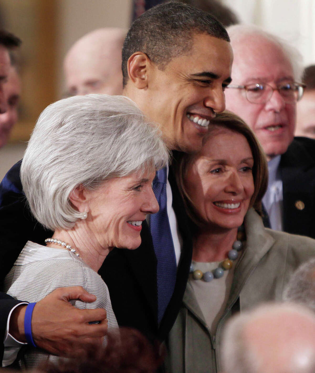 FILE - In a March 23, 2010, file photo President Barack Obama embraces Health and Human Services Secretary Kathleen Sebelius, left, and House Speaker Nancy Pelosi of Calif. in the East Room of the White House in Washington after he signed the health care bill. Obama and Pelosi devoted a vast amount of his first term to passing a health care law that has divided the nation. By winning at the Supreme Court, Obama and his party preserve historic legislation, that liberals have been pining for for more than 50 years. (AP Photo/Charles Dharapak, File)