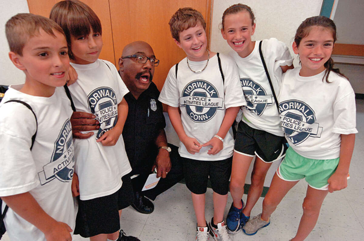 Norwalk police officer Carleton Giles, who has been DARE coordinator for 15 years, says goodbye to his campers during the DARE graduation reception Friday at police headquarters. Giles will be retiring next year. Hour photo / Erik Trautmann