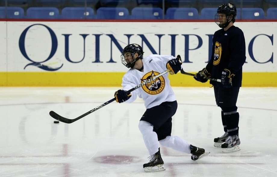 Quinnipiac forward Jeremy Langelois, left, shoots during an optional practice at the university in Hamden, Conn., Tuesday, April 2, 2013. Quinnipiac will face North Dakota in a national semifinal at the NCAA hockey Frozen Four. At right is forward Clay Harvey. (AP Photo/Charles Krupa) / AP
