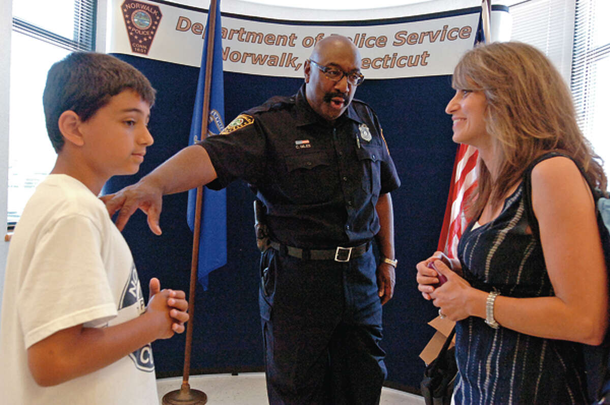 Norwalk police officer Carleton Giles, who has been DARE coordinator for 15 years, says goodbye to his campers including Christopher Montoya and his mother, Maria Montoya during the DARE graduation reception Friday at police headquarters. Giles will be retiring next year. Hour photo / Erik Trautmann