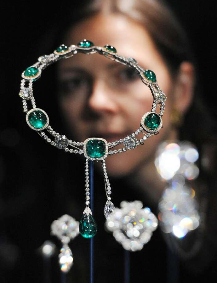 This Thursday June 28, 2012 photo shows curator Caroline de Guitaut, standing behind the Delhi Durbar Necklace and Cullinan Pendant made up of diamonds and emeralds, created for the Delhi Durbar of 1911 and owned by Queen Mary, at a new exhibition at Buckingham Palace, London. The new exhibition at Buckingham Palace shows jewels collected by six monarchs over three centuries to mark the Queen's Diamond jubilee this summer. (AP Photo/Stefan Rousseau/PA Wire) UNITED KINGDOM OUT NO SALES NO ARCHIVE
