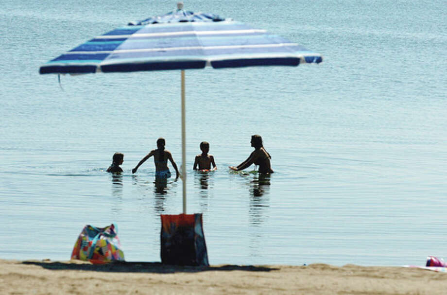 A family enjoys the cool waters at Calf Pasture Beach recently.Hour photo / Erik Trautmann / (C)2012, The Hour Newspapers, all rights reserved