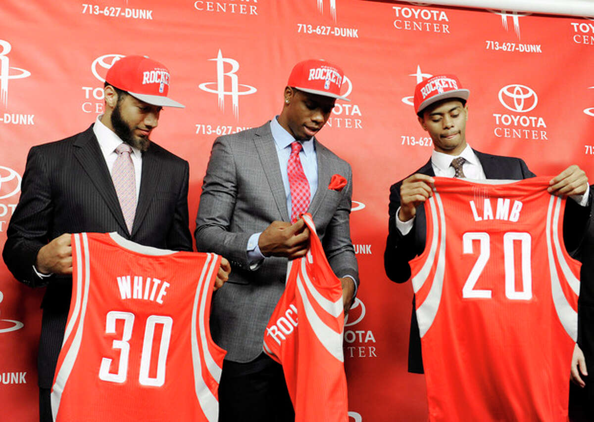Houston Rockets first-round draft picks Royce White, left, Terrence Jones, center, and Jeremy Lamb pick up their jerseys at a news conference on Friday, June 29, 2012, in Houston. (AP Photo/Pat Sullivan)