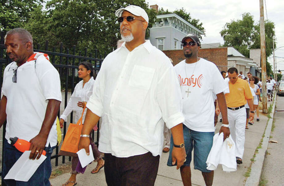Hour photo / Erik TrautmannThe Rev. Lindsay Curtis, pastor at the Grace Baptist Church, walks in the The SoNo Alliance Prayer Walk Saturday where religious leaders and the NPD urged residents to become more involved in their community. / (C)2012, The Hour Newspapers, all rights reserved