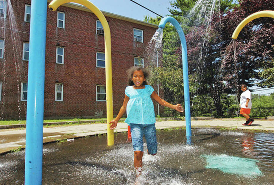 Hour photo / Erik TrautmannShamarra Figueroa, 9, runs through the spash pad at Roodner Court Saturday in a effort to beat the heat. / (C)2012, The Hour Newspapers, all rights reserved