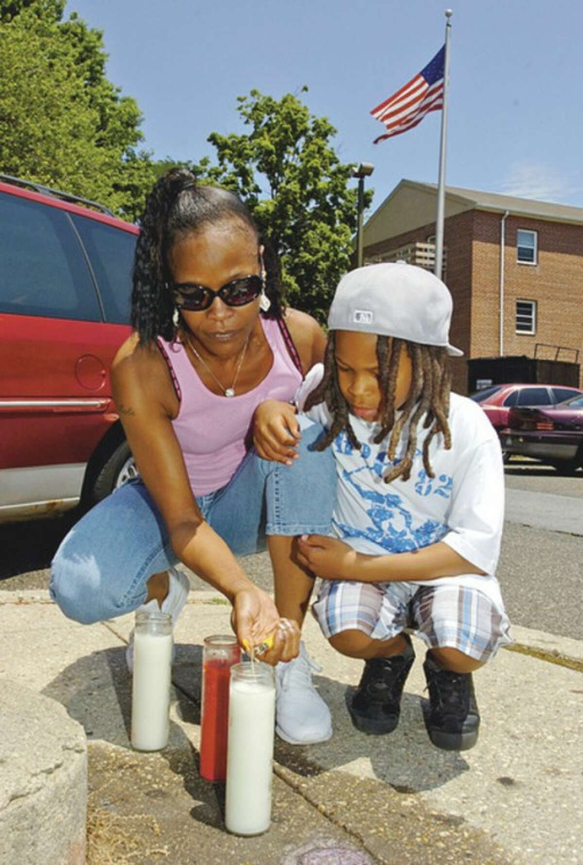 """Hour photo / Erik Trautmann Honoring Dad Natacha Moore and her son, LaRay Moore Jr., 7, lay candles at the site where LaRay Moore Sr. was killed on June 29, 2006. He was gunned down in his car near building 12 at Roodner Court while picking up his son -- then 15-months-old -- from his aunt's apartment. """"I can close my eyes, and it feels like it just happened yesterday,"""" Natacha Moore said. Although hundreds of people were outside when LaRay Moore Sr. was killed, police have not received viable information from any witnesses. The case was recently reassigned to Detective Shannon Sherry. Police are asking anyone with information on the case to call (203) 854-3011."""